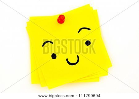 Smiling face against sticky note with red pushpin