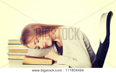 Tired woman slepping on books.