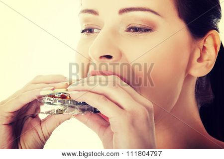 Woman eating too many pills.