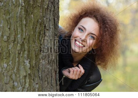 Portrait of a happy woman with curly hair peeking out from behind a tree in autumn park