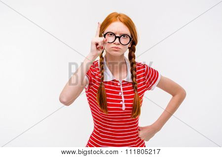 Strict young redhead woman with two braids in round glassees pointing up isolated on white background