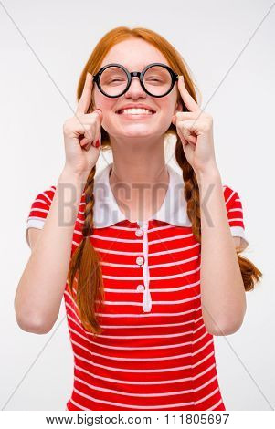 Cheerful pleased funny young female with two braids fixing round glasses and smiling isolated over white background