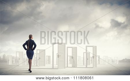 Businesswoman standing in front of opened doors and making decision