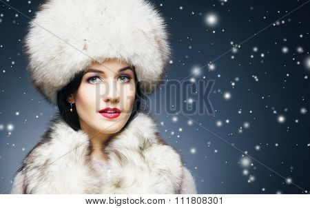 Fashion style portrait of a woman in an elegant winter fury clothes over snowy night background.
