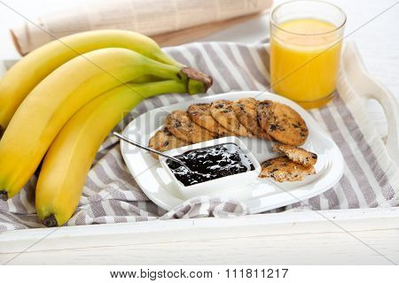 Plate of tasty cookies with chocolate crumbs, jam, bananas and orange juice on striped cotton serviette