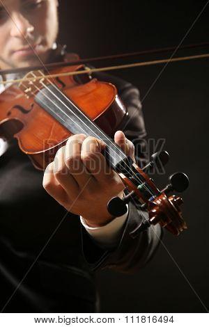 Violinist's performance on black background, close up