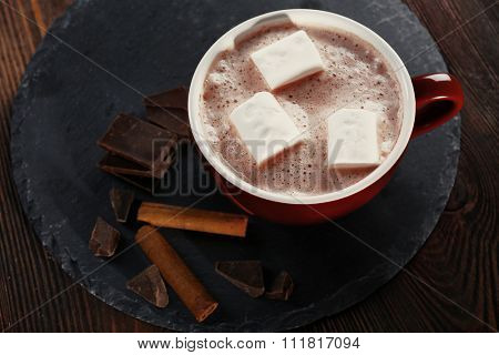 Cup of hot cacao with marshmallow, cinnamon and sweets on blue serviette, close up