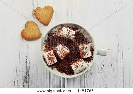 Cup of hot cacao with marshmallow and heart shaped cookies on cotton serviette, close up