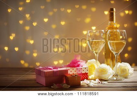 Glasses of wine, white roses a gift in the box and a bottle, on blurred background