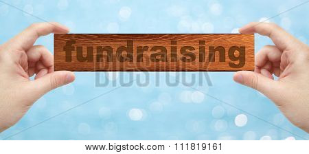 Hands Holding A Wood Engrave With Fundraising
