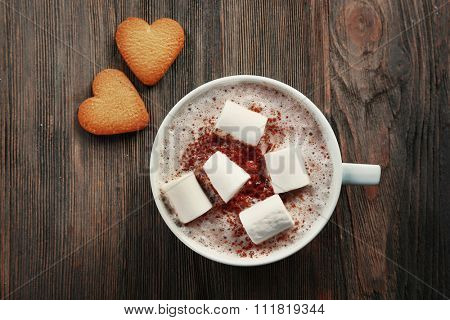 Cup of hot cacao with marshmallow and heart shaped cookies on wooden background