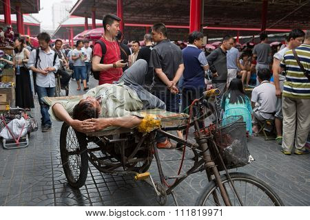 BEIJING - CIRCA JUNE, 2015: Rickshaw Man resting on a rickshaw being on the famous Panjiayuan Antique Market - one of the best antiques market in China. Area shopping area of 48 500 м2.