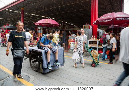 BEIJING - CIRCA JUNE, 2015: European boy sitting on a trishaw and uses smartphone being on the Panjiayuan Antique Market - one of the best antiques market in China. Area shopping area of 48 500 м2.