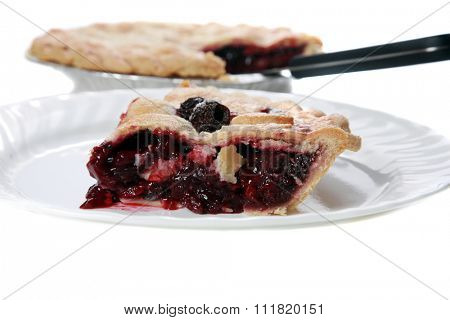 a slice of fresh berry pie on a white plate with the remainder in the background. focus on the front of the slice of berry pie. isolated on white with room for your text