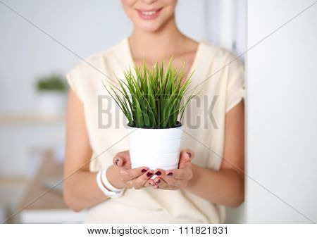 Beautiful woman holding pot with a plant, standing at home