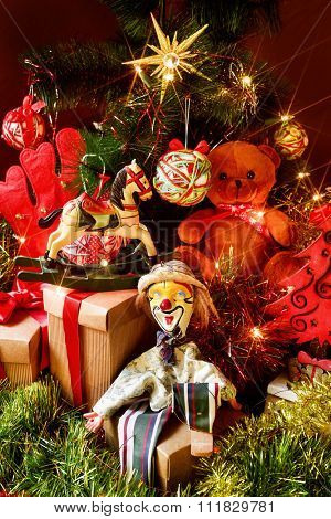 some gifts and some retro toys, such as a teddy bear, a horse or a marionette, under a christmas tree ornamented with a christmas star, lights, balls and tinsel