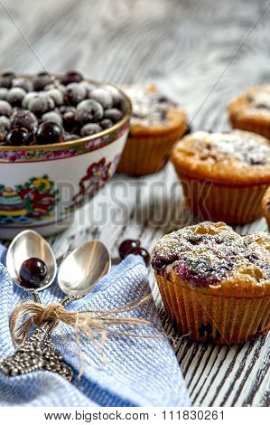 Muffins, a Cup of blackcurrant and two silver spoons