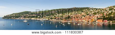 Wide panoramic view of French Riviera coast at Villefranche-sur-Mer harbour and Cap de Nice with leisure boats anchored at Mediterranean sea