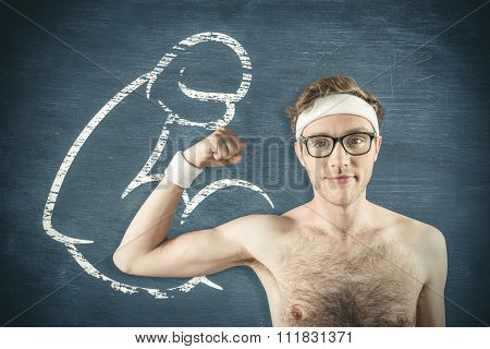 Geeky shirtless hipster flexing bicep against blue chalkboard