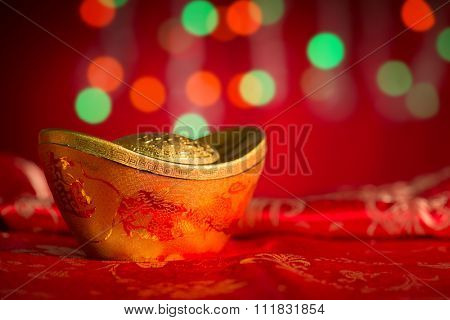 Chinese new year festival decorations, single gold ingot on red glitter background.