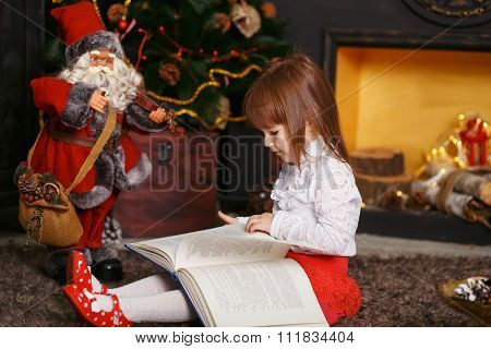 Girl Reading A Fairy Tale Toy Santa Claus
