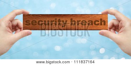 Hands Holding A Wood Engrave With Word Security Breach