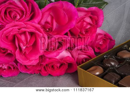 Bright Pink Roses and Gourmet Chocolates on Gray Tulle Background