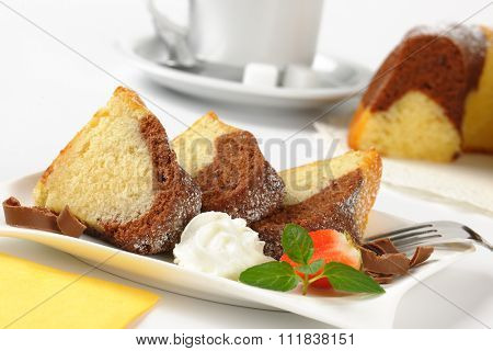detail of marble bundt cake slices and whipped cream on white plate