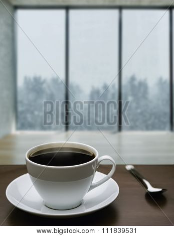 A cup of coffee and snowstorm view from large window on the background