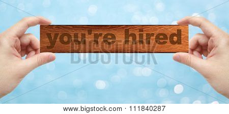 Hands Holding A Wood Engrave With Word You're Hired