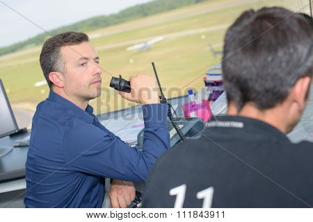 Man talking into receiver in air traffic control