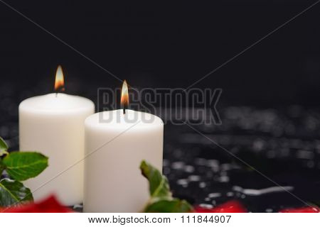 red rose with two white candle and therapy stones