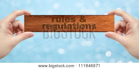 Hands Holding A Wood Engrave With Word Rules & Regulations