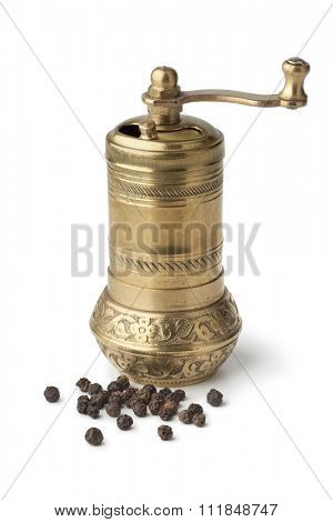 Traditional oriental bronze pepper mill and black pepper on white background