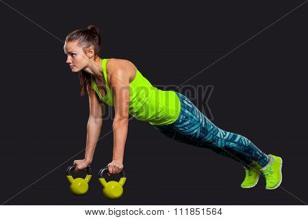 Fitness woman in plank position with kettlebells a gray background.