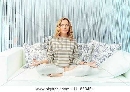 Happy young woman having a rest in her bedroom and doing yoga exercises. Home interior, furniture. Lifestyle.