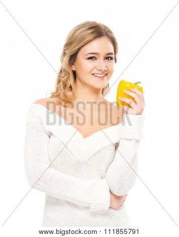 Young and beautiful woman in white cardigan being healthy with yellow paprika on isolated background.
