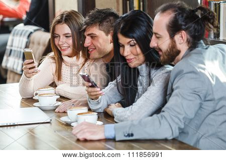 Group of friends ein cafe looking at smartphones
