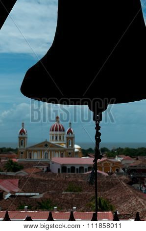 Silhouette of a bell over chuch and house rooftops in city Granada