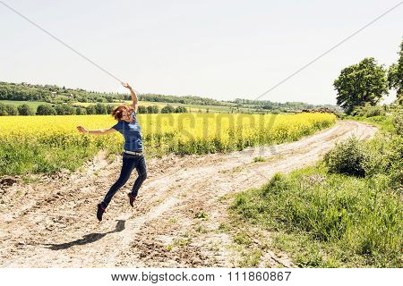 Joyful Young Woman Is Jumping In Rapeseed Field
