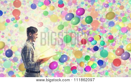 Young man student with book in hands among colorful balloons