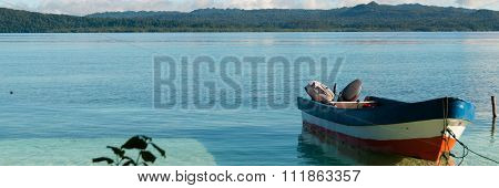 Small wooden boat in shallow clear water tied up by the white sand beach