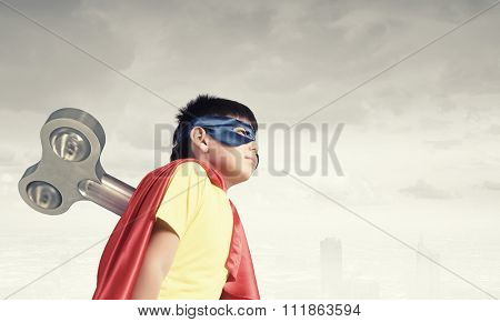 Little super active boy with key on back wearing super hero costume