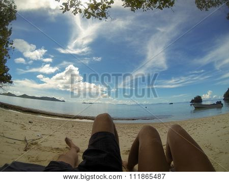 Feet of two person laying on sand beach under blue sky relaxing in Raja Ampat, Papua New Guinea