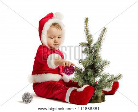 Funny Baby In Santa Claus Clothes  Is Decorating Xmas Tree On White Background