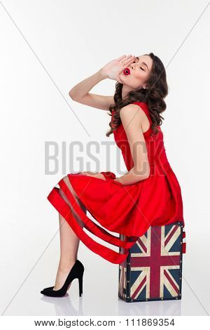 Beautiful curly young female in retro style red dress sitting on vintage suitcase and calling for somebody