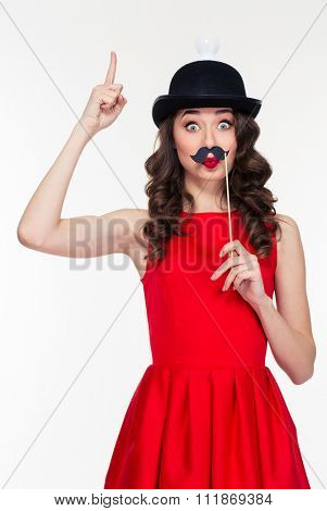 Playful hilarious young curly woman in red dress and funny black hat with light bulb having fun with moustache props and pointing up