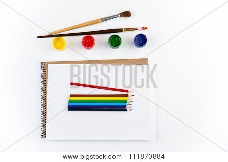 Top view of sketchbook, paintbrushes, colorful pensils and gouache paints isolated over white background
