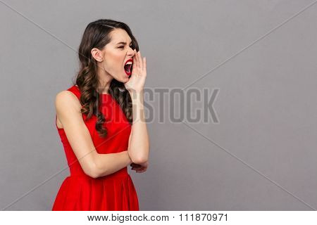 Side view portrait of a young woman in red dress screaming over gray background