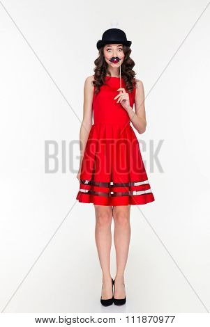 Full length of comical amusing young woman in red dress and ridiculous black hat with light bulb holding fake moustache on stick